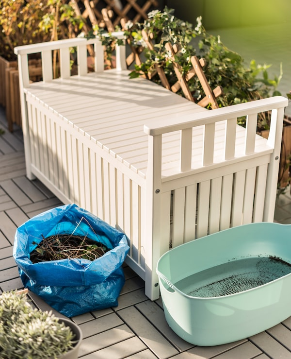 A white bench with storage, a plastic tub filled with rain water, and a blue IKEA bag filled with compost sit in the garden.