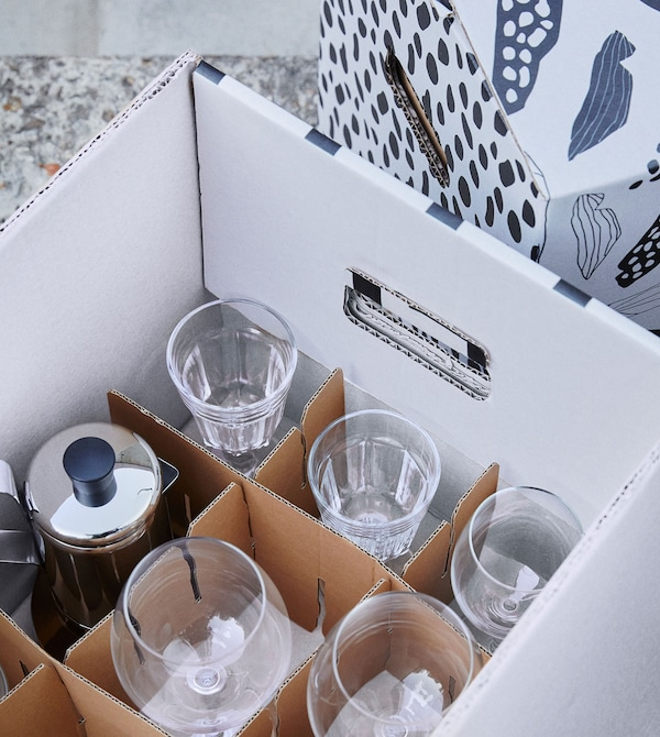 A white box with a brown OMBYTE divider, filled with a variety of clear wine glasses.