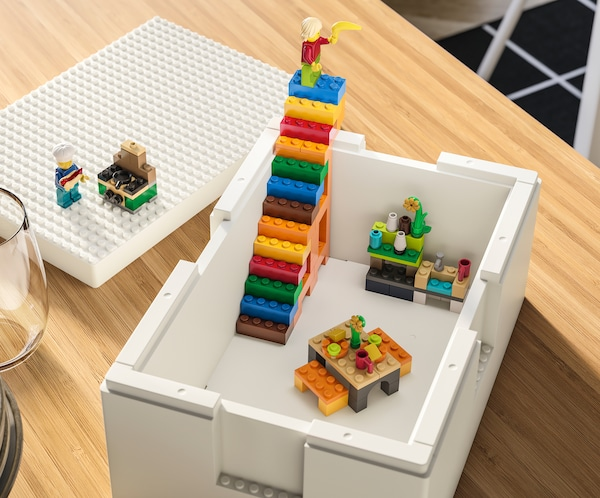 A white BYGGLEK box stands on a table, with brightly-coloured LEGO constructions, including a set of stairs, inside it.
