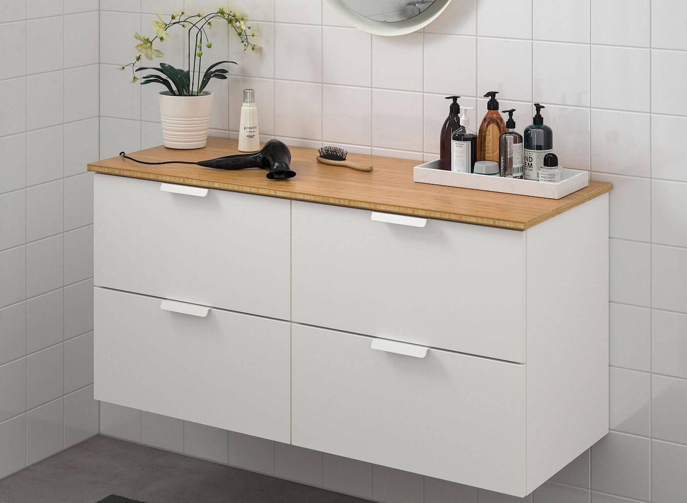 A white cabinet mounted on the wall with four drawers and a wood counter top, and various bathroom accessories on top.