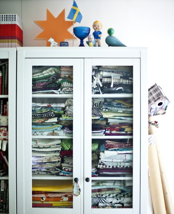 A white cabinet with glass doors filled with fabric.
