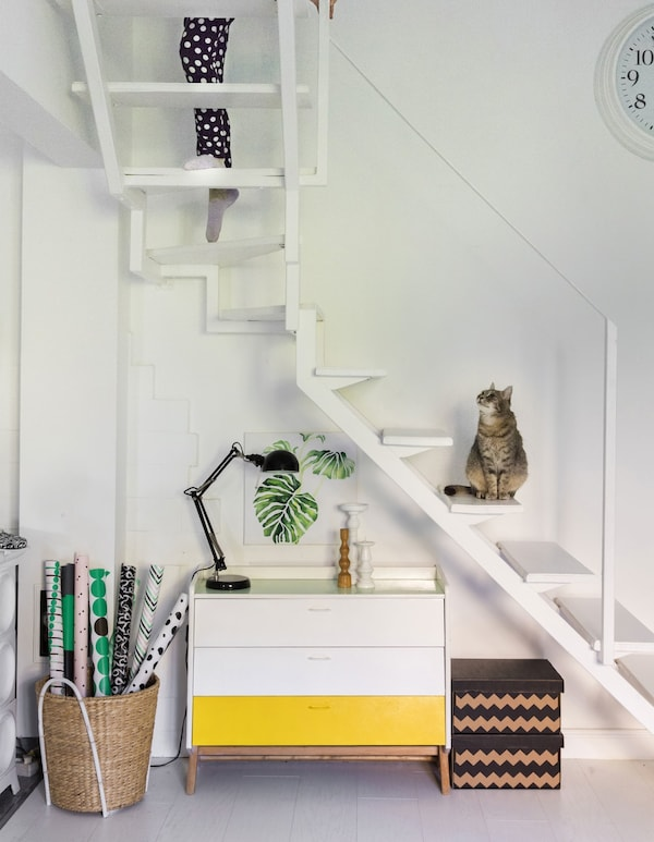 A white cabinet with one yellow drawer, placed under white, floating stairs.