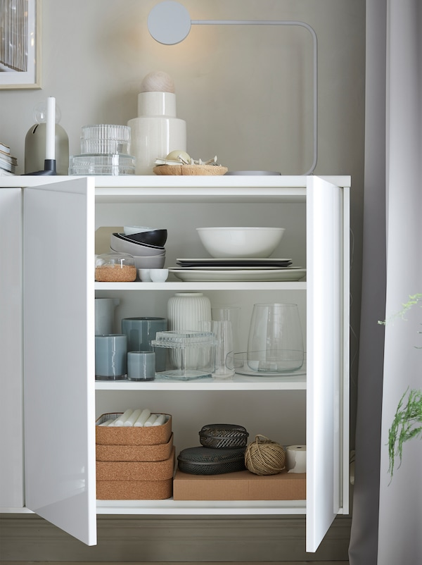 A white cabinet with open white high-gloss doors showing tableware, vases and candles inside and a lamp on top.