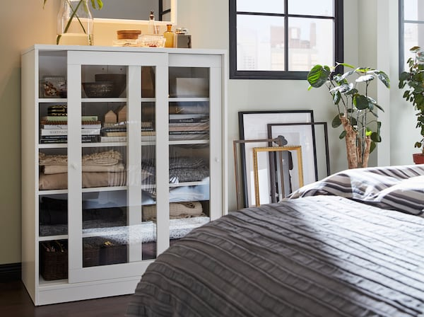 A white cabinet with sliding glass doors, frames that stand against a wall and a grey bedspread.
