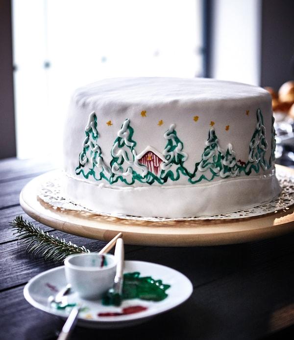 A white cake hand painted with a Christmas scene sits on an IKEA SNUDDA lazy Susan.