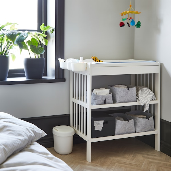 A white changing table with grey open boxes on its shelves. Beside is a window with dark grey plant pots on the window sill.