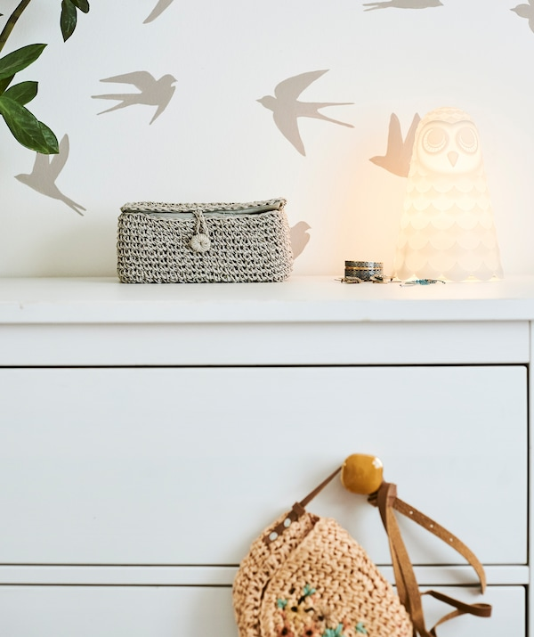 A white chest of drawers with amber-colored handles and an owl light on top, pushed against a wall with birds stencil motif.