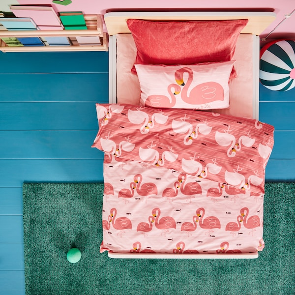 A white children's bed frame with a pink bedsheet and bed textiles with flamingo patterns, a green rug and a round soft toy.
