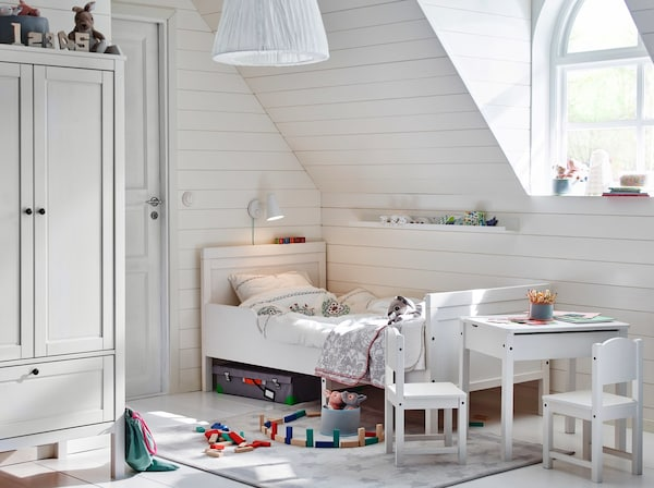 A white children's bedroom with colourful building blocks on floor.