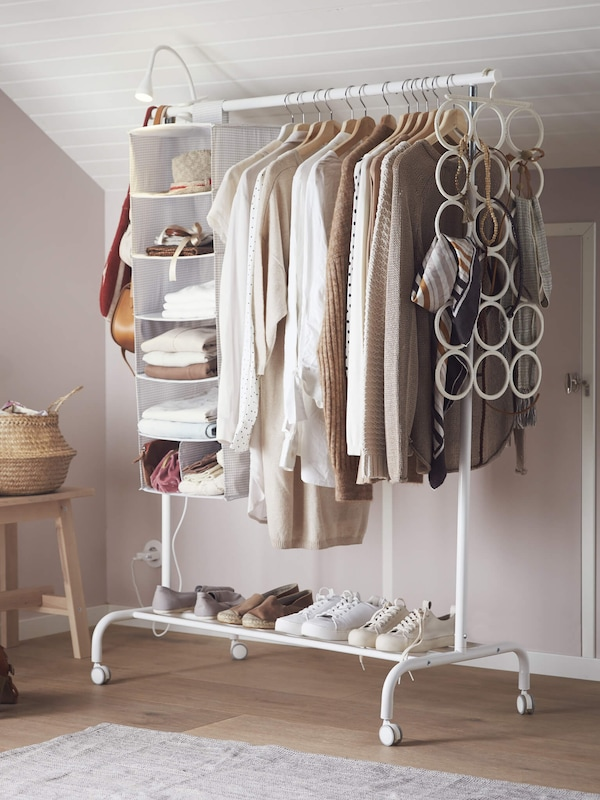 A white clothes rack with shirts hanging on hangers and shoes on the bottom rack, linking to the clothes organizers page.