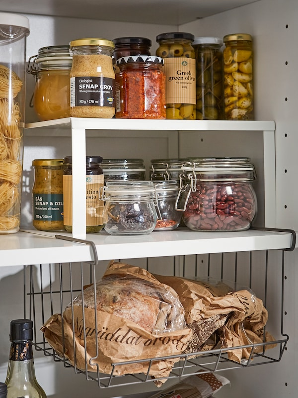 A white coated steel shelf insert and metal clip-on basket inside a pantry shelving space for jams, jars, and bottles.