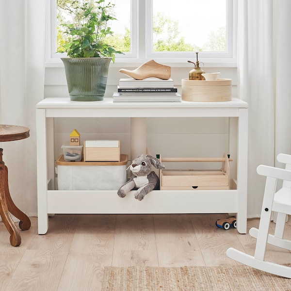A white console table with toys stored in boxes and baskets.