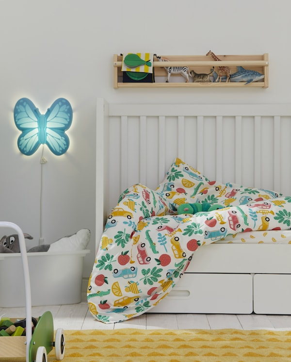 A white cot with colourful and patterned bed linen, a butterfly-shaped wall lamp, a yellow rug and toys on wall storage.