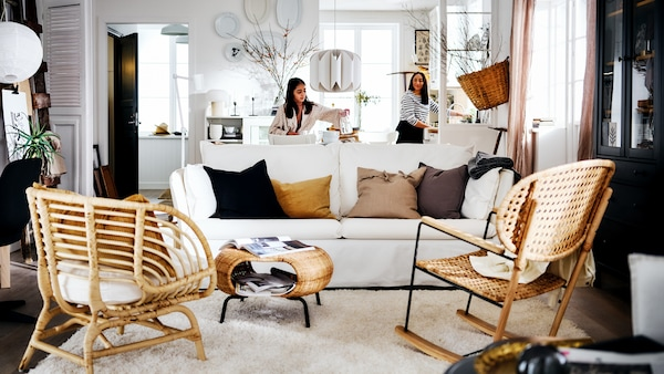 A white country-style living area with two women behind a white BACKSÄLEN sofa that's in front of a rug and two armchairs.