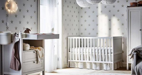 A white crib in a room with a white changing table, paper shade lamps hanging from above and a star patterned wallpaper.