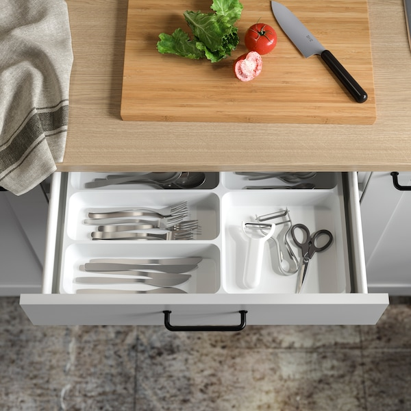 A white cutlery tray is placed inside an open kitchen drawer and shows divided and organised cutlery and more.