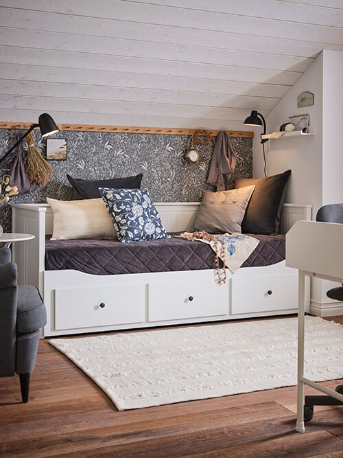 A white daybed arranged as a sofa, cushions in different colours, a dark grey bedspread, lamps.