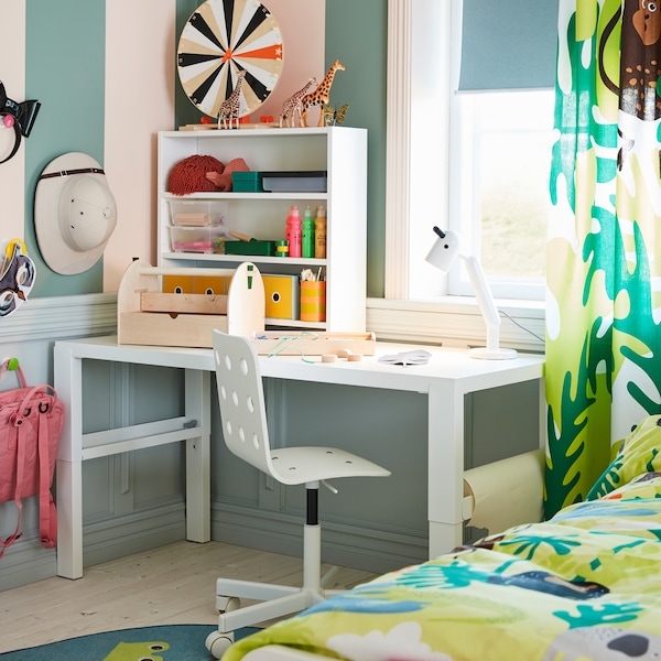 A white desk, a white children's desk chair, a white table lamp and curtains in a jungle pattern.