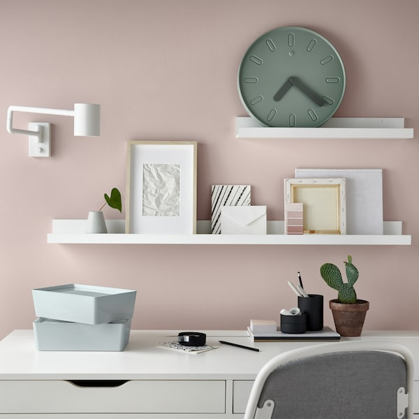 A white desk against a pale pink wall, with picture frames and a clock displayed on white picture ledges.