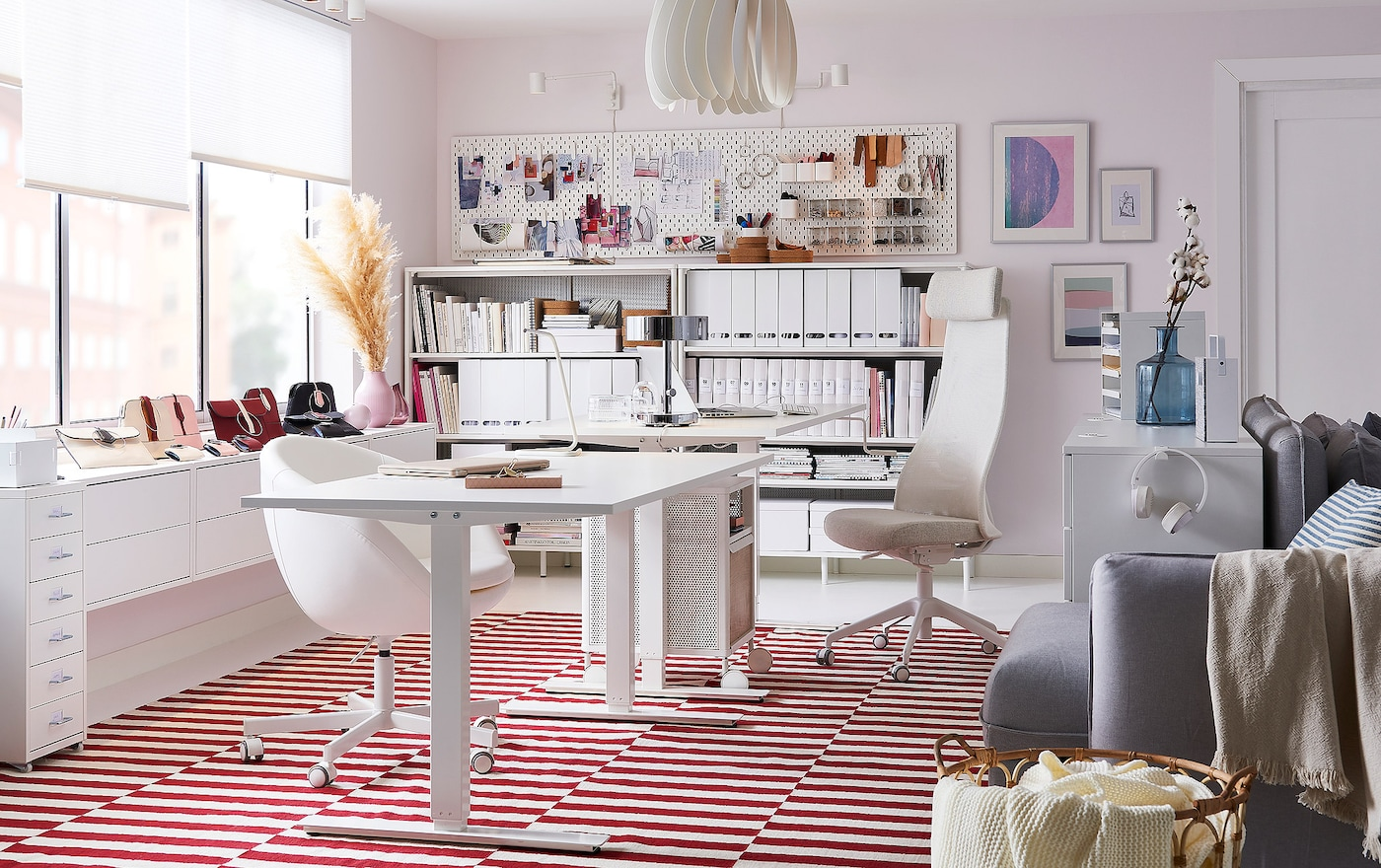 A white desk on a white and red rug with a rollable storage unit and white office drawers.