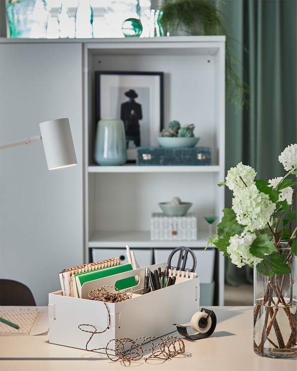 A white desk organiser is placed on a white desk in a bedroom, and it holds pens, scissors, notebooks and more.