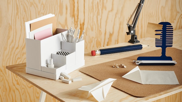 A white desk organizer on a desk with notepads, erasers, a pencil and paper nearby, with a wooden wall in the background.