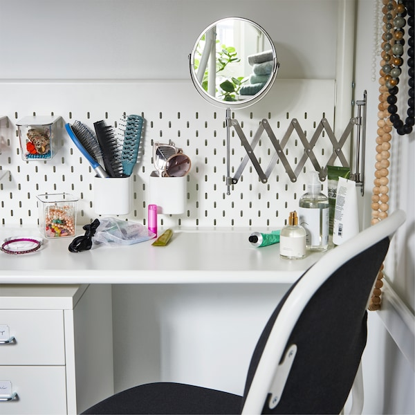 A white desk under a loft bed with a mirror that's mounted on the wall. Hair tools are stored on the loft bed's pegboard.