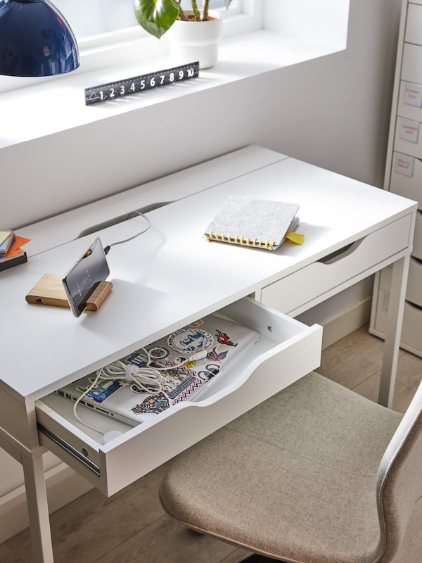 A white desk with one drawer pulled out with a laptop inside, linking to the tables and desks page.