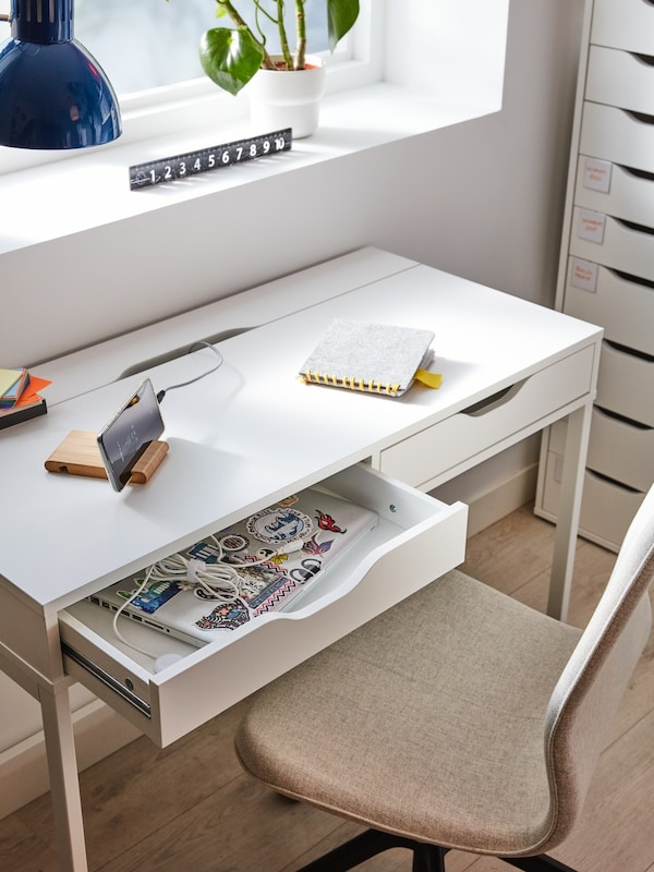 A white desk with open drawer. There is a white work lamp too.