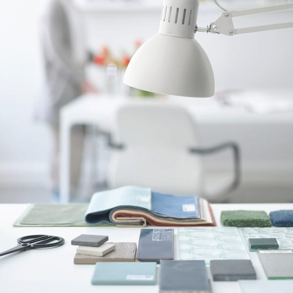 A white deskt with green and blue samples on the top, also with a white desk lamp