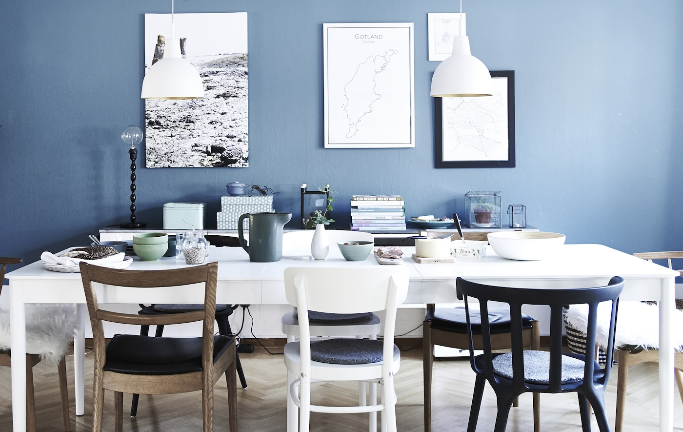 A white dining area against a blue wall.