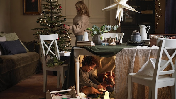 A white dining table set in a dark lit family home. Young boy sitting underneath table with small light glowing, playing with dinosaur soft toy. Woman in background decorating Christmas tree in living room.