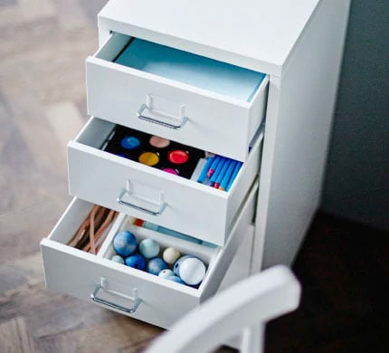 A white drawer unit on casters with three of the drawers open