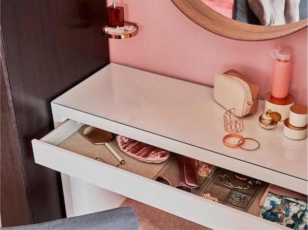 A white dressing table, a round mirror, a black-brown wardrobe and a display shelf in metal and glass.