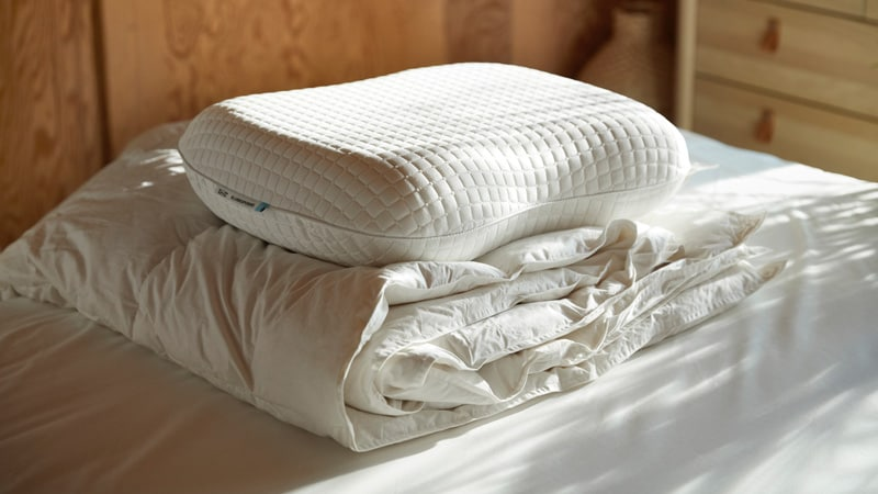 A white duvet and an ergonomic pillow on a bed.