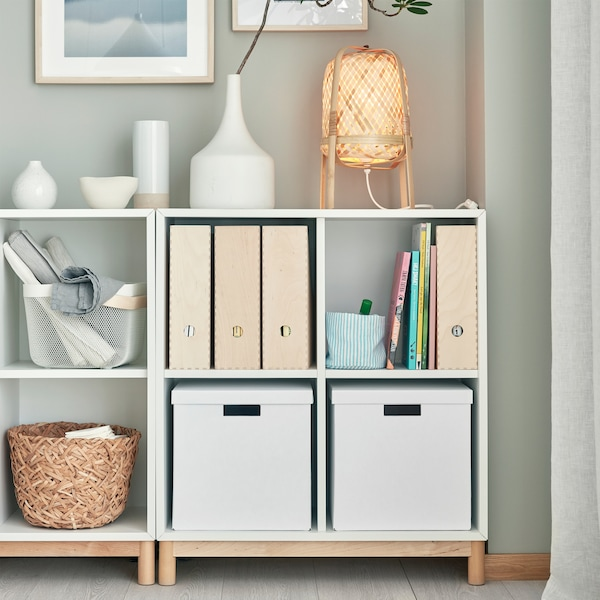 A white EKET cabinet combination with legs in birch. Different storage boxes and decorations stand on the shelves and on top.