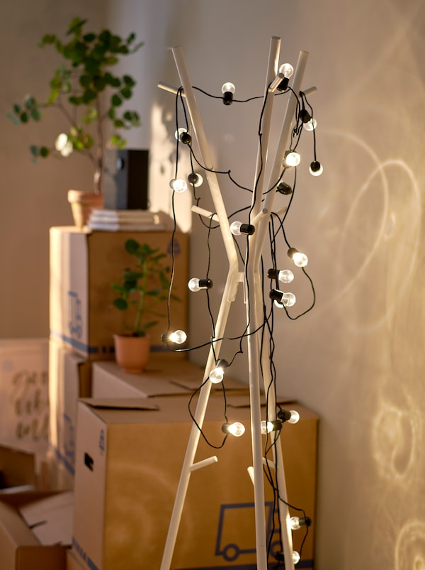A white EKRAR hat and coat stand wrapped in a lit BLÖTSNÖ LED lighting chain, standing next to stacked moving boxes.