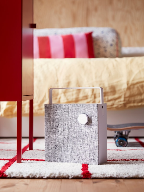 A white ENEBY Bluetooth speaker stands on a white and red rug in a modern, bright, wood-panelled bedroom.