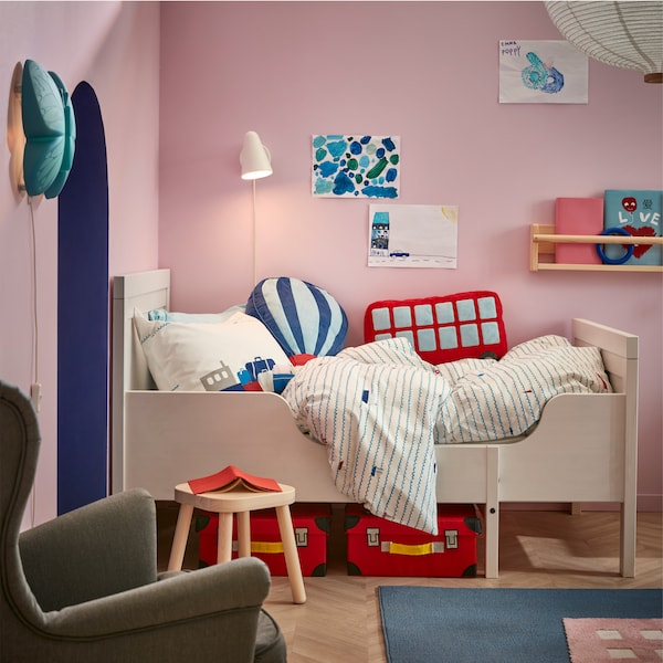 A white extendable children's bed frame with boat patterned bed textiles and above is a white wall lamp that's lit.