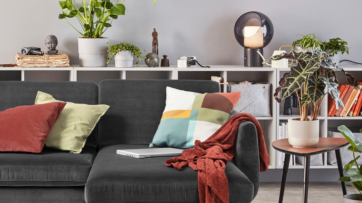 A white FÄRLÖV sofa with different cushions and a throw sits near a black table and a REGNSKUR pendant lamp.