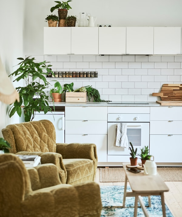 A white galley kitchen with metro tiles, two retro green armchairs and an Oriental-style rug, with a bench used as a table.