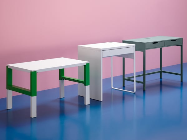 A white/green PÅHL desk, a white MICKE desk and a grey-turquoise ALEX desk in a set with a pink wall and blue floor.