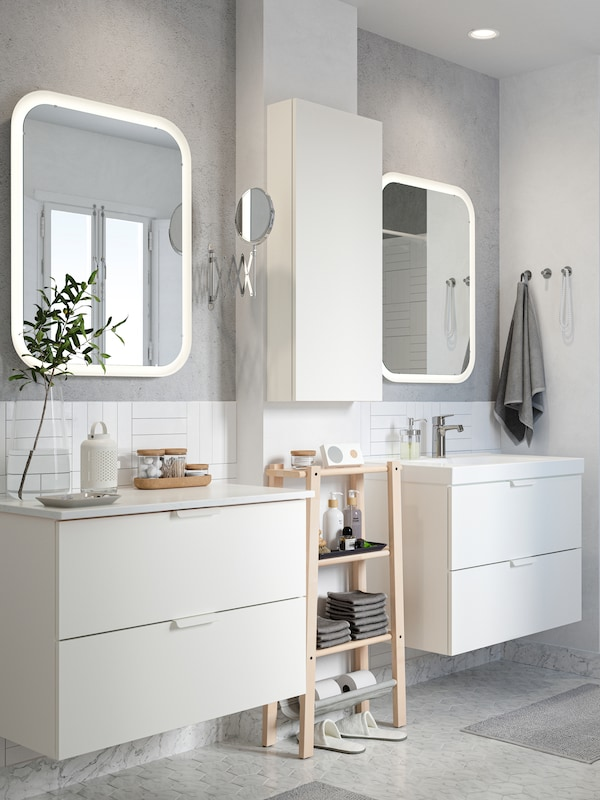 A white/grey bathroom with two GODMORGON wash-basins and mirrors. A VILTO shelving unit in birch is placed between.