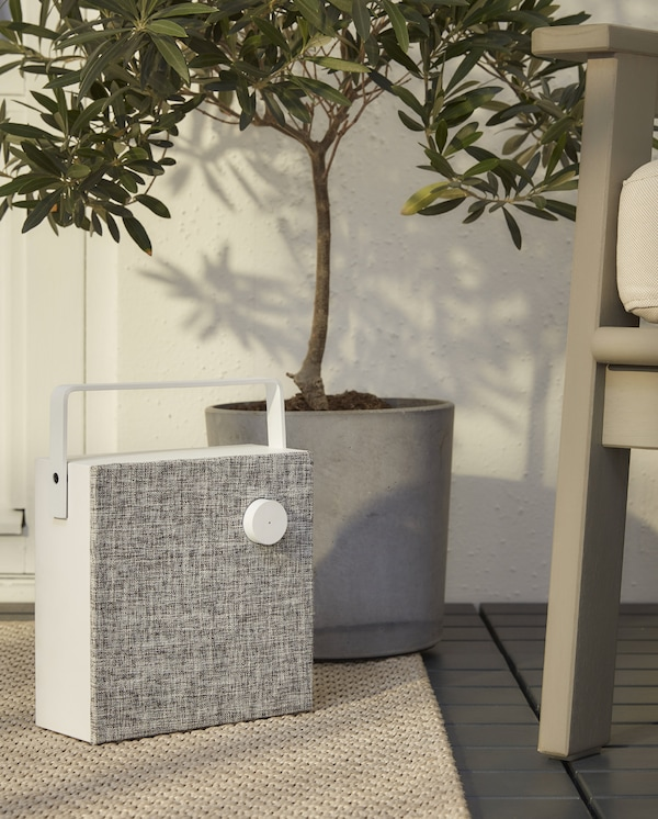 A white/grey, square and cordless speaker with handle stands on a beige rug next to a grey outdoor armchair.