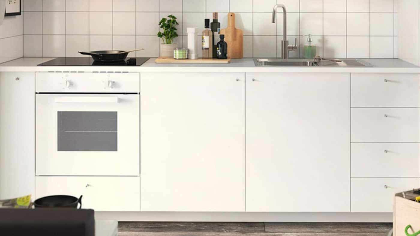 A white HAGGEBY kitchen with white worktop and stainless steel handles.
