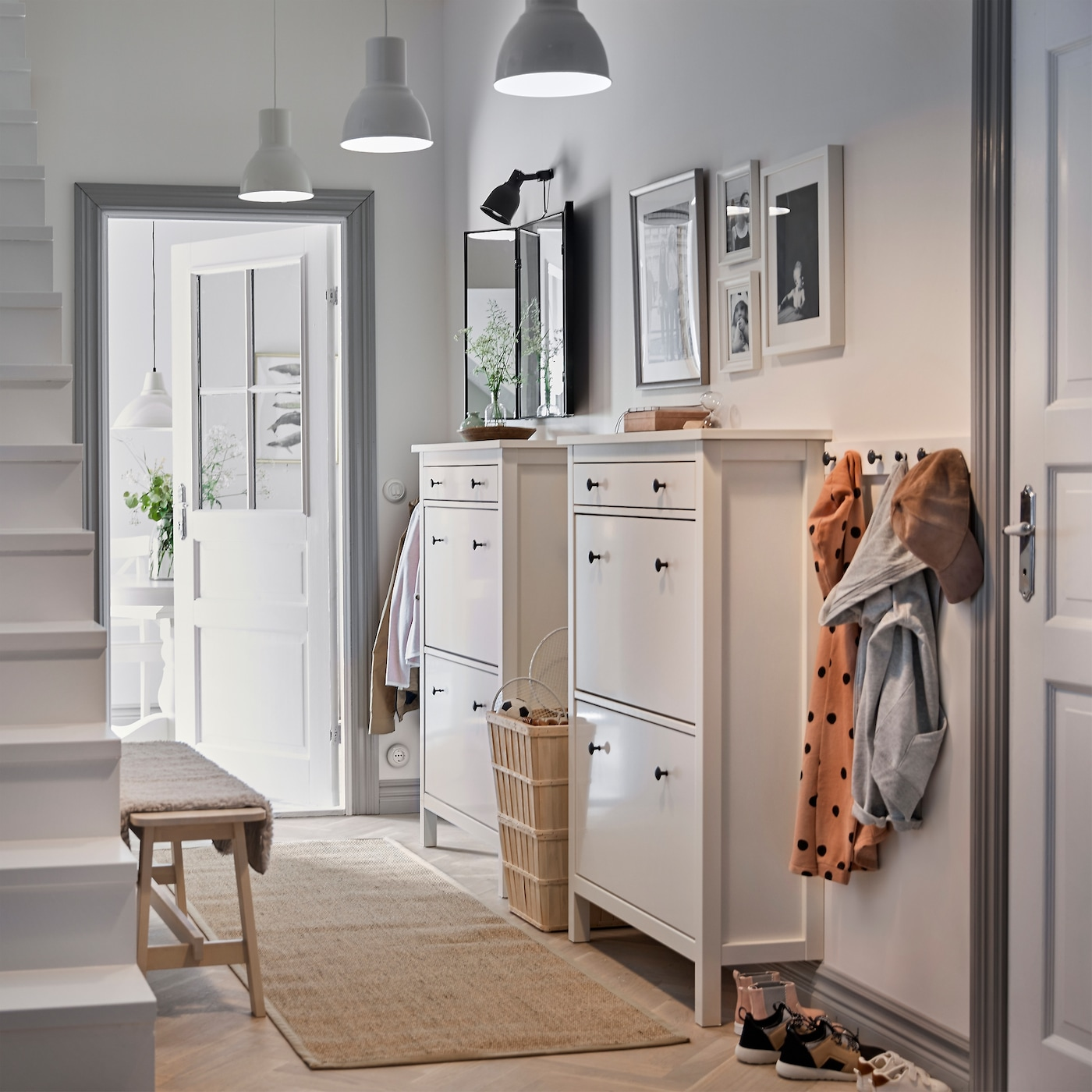 A white hall with two traditional white HEMNES shoe cabinets next to each other and a coat rack for the coats.