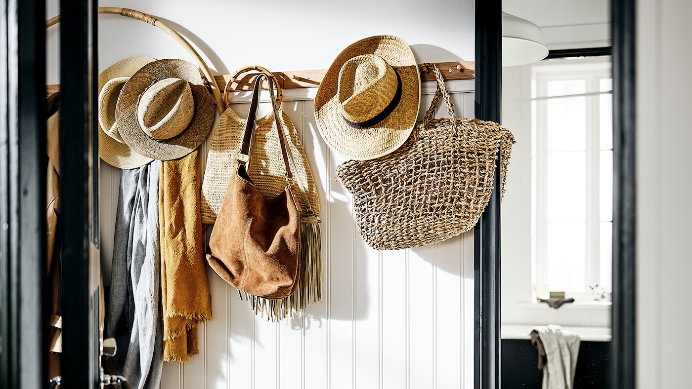 A white hallway with a rack with six knobs holding bags, hats and scarves in natural colours, and a TOFTBYN mirror beside it.