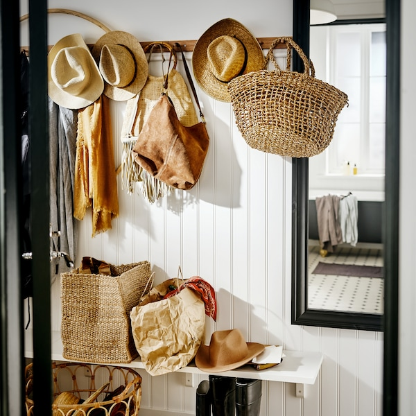 A white hallway with racks with six knobs holding bags, hats and scarves in natural colours, beside a TOFTBYN mirror.