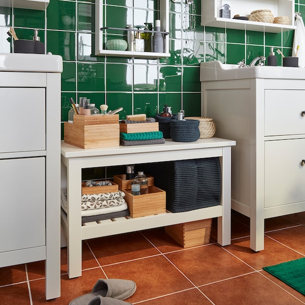 A white HEMNES bench stands between two wash-basins. Boxes and towels are stored on the bench shelves.