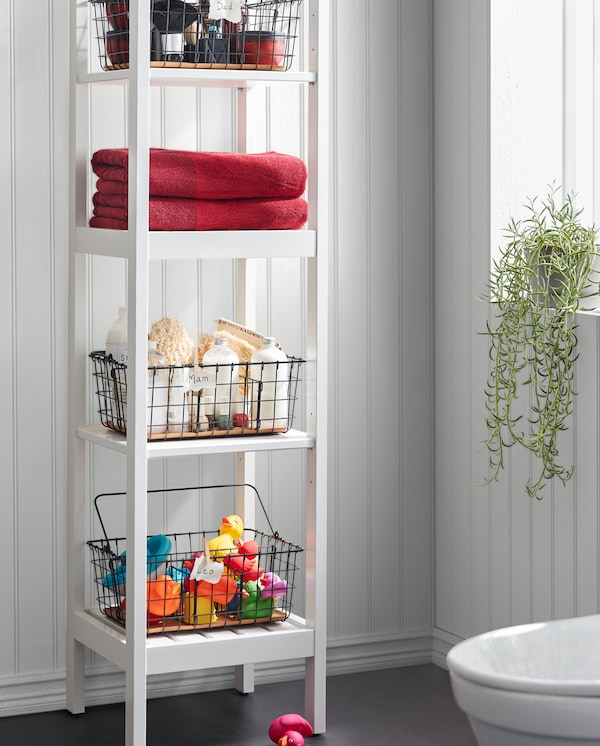 A white HEMNES shelf unit with black PLEJA wire baskets storing towels, bath toys, spa stuff and more on the four shelves.